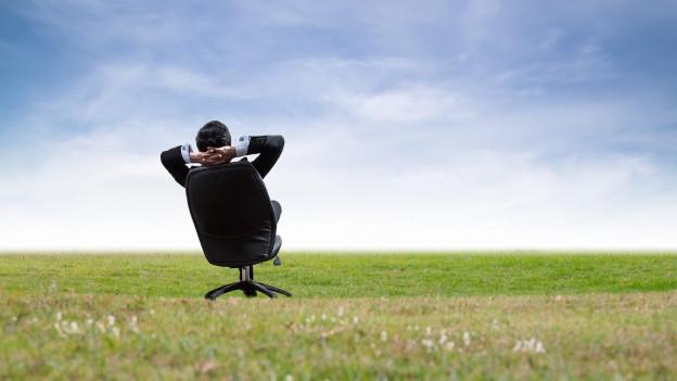 Ein Mann in Anzug sitzt auf einem Bürohstuhl mitten in einer Wiese und entspannt sich.