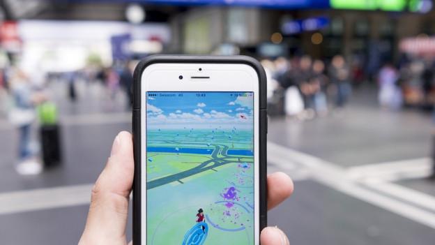 Ein Handybildschirm mit Pokémon-go-Spieloberflläch im Vordergrund, unscharf im Hintergrund die Bahnhofshalle des Hauptbahnhofs Zürich.