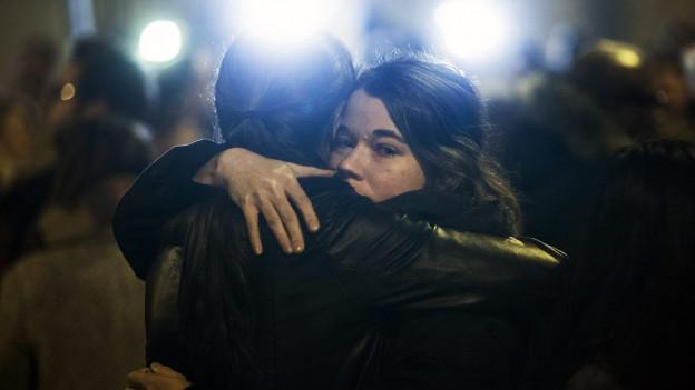 Eine Frau umarmt eine Kollegin. Der Schreck steht ihr ins Gesicht geschrieben.