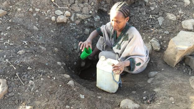 Eine Frau in Äthiopien sucht verzweifelt nach Wasser aus einer vertrockneten Quelle
