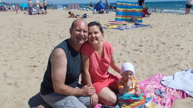 Eugen Stulz mit Frau Joanna und Sohn John sitzen im weissen Sand am Strand von Bournemouth.