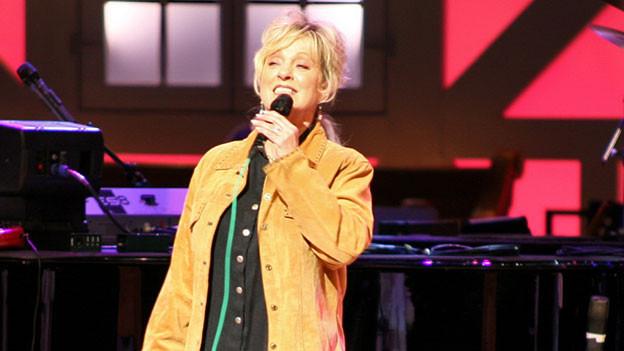 Connie Smith steht auf der Bühne und singt.