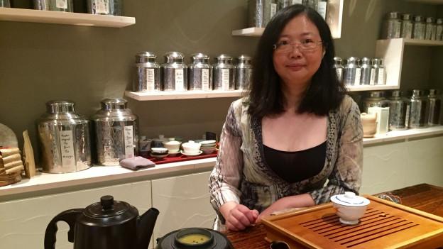 Die Taiwanesin Meng-Lin Chou posiert in ihrem Teeladen. Vor sich hat sie Teegeschirr.