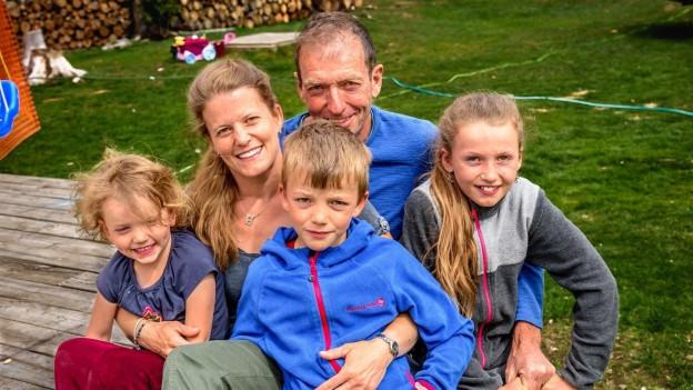 Famielie Perren: Vater Robert, Mutter Carmen, Töchter Anju und Ava zusammen mit Bruder Lou sitzen vor ihrem Blockhaus am Wheaton River.