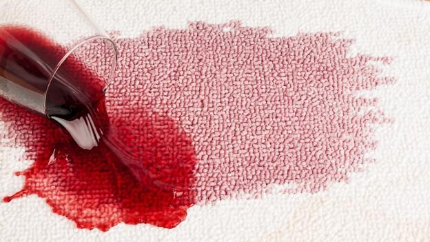 Rotweinflecken auf weissem Teppich.