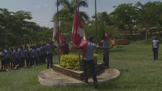 Schüler ziehen drei Fahnen am Mast hoch: die von Kamerun, die der Schweiz und die des Kantons Jura