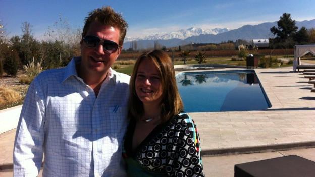 Norbert und Andrea Aellen stehen auf einem Luxus Weingut in Argentinien. Im Hintergrund sind ein Swimmingpool und die argentinischen Anden zu sehen.