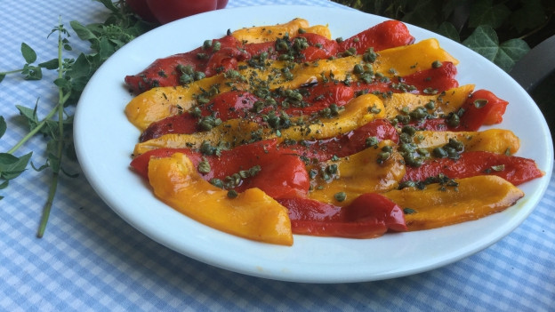 rote und gelbe geschmorte Peperoni mit Kapern auf einer weissen Platte.