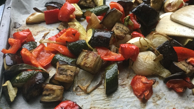 Zucchetti, Peperoni, Frühlingszwiebeln und Auberginen auf einem Blech im Ofen gebacken.