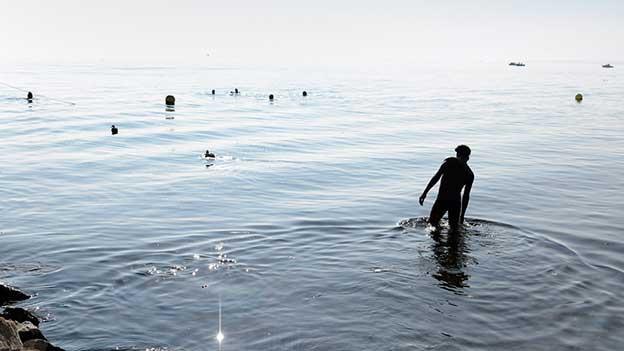 Mann geht im Genfersee baden.