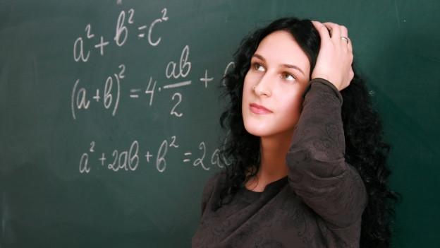 Ratlose Kandidatin vor einer Wandtafel mit mathematischen Formeln