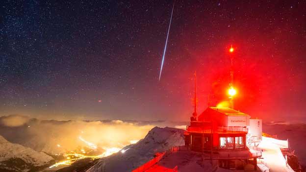 Eine Sternschnuppe am Himmel über der Bergstation Corvatsch.