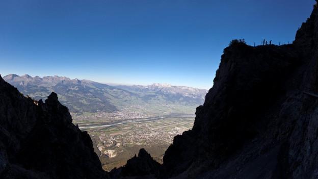 Eine Gebirsgkrete im Gegenlicht, hoch über dem Rheintal, am rechten Bildrand sieht man die Silhouetten einer Wandergruppe.