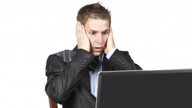 Junger Mann entsetzt darüber, was er auf dem Laptop liest