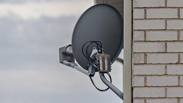 Satellitenschüssel an Hauswand.