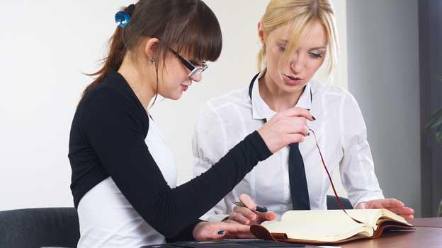 Zwei Frauen reden im Büro.