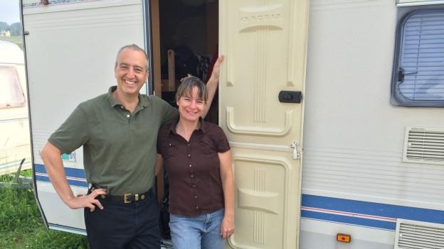 Henry Camus und Gaby Schmutz posieren vor ihrem Wohnwagen.