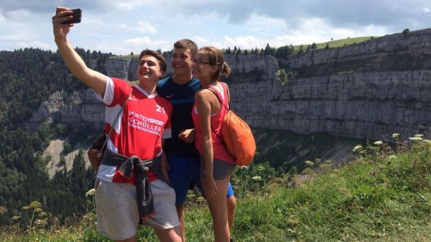 Drei Jugendliche stehen auf dem Creux du Van hoch über dem Neuenburgersee und machen ein Selfie.