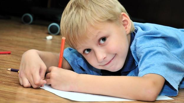 ein Knabe an einem Tisch, der auf ein weisses Blatt vor ihm mit dem Füller in der linken Hand beschreibt.