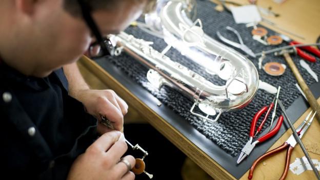 Ein Lehrling von oben fotografiert, der hochkonzentriert an einem Saxofon-Modell arbeitet, auf dem Tisch Zangen und Kleinteile.