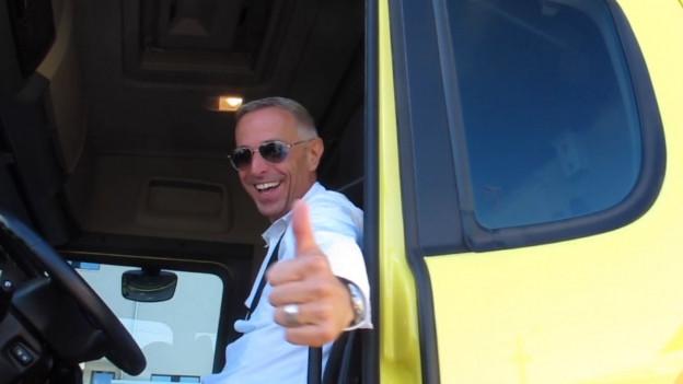 SRF1-Moderator Dani Fohrler im weissen Hemd und Sonnenbrille im Cockpit eines gelben Scania-Lastwagens.