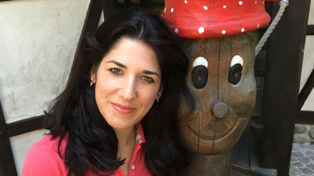 Lucie Hippenmeyer aus Münchenstein, Baselland, trägt ein rotes T-Shirt. Sie posiert vor einer lebensgrossen Holzfigur mit einem roten Topf auf dem Kopf.