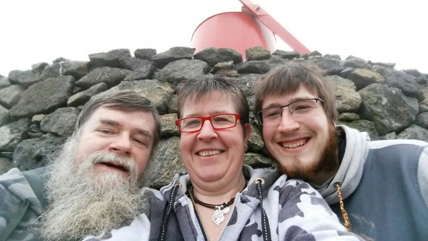 Von links: Vater Thomas, Mutter Claire Dellenbach und Sohnemann Iwan. Sie stehen vor einem Steinhaufen.