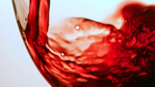 Rotwein wird in Glas gegossen.