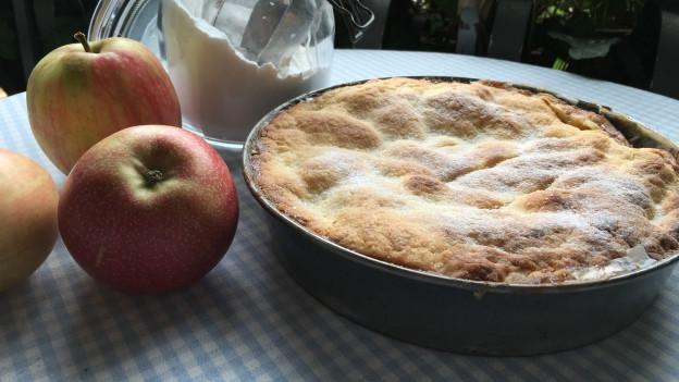 Gedeckter Apfelkuchen und frische Äpfel auf einem Tisch.