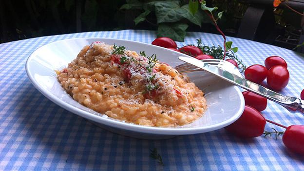 Tomaten-Geisskäse-Risotto auf einer ovalen Platte.