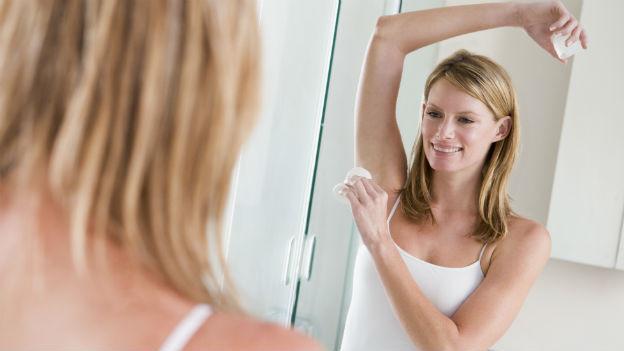 Frau streicht sich vor dem Spiegel Deo unter den Arm.