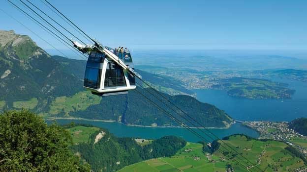 Doppelstöckige Bahn unterwegs auf den Berg, im Hintergrund Berge und der See.