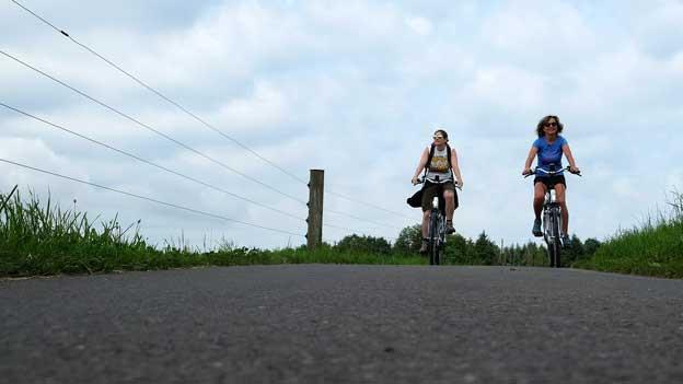 Zwei Frauen fahren auf dem E-Bike.