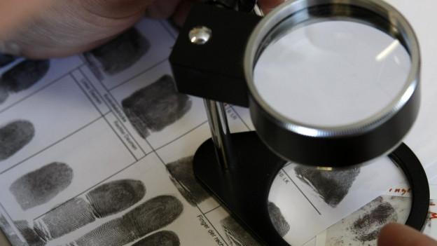 Ein Kriminalist schaut mit einer Lupe eine Reihe von Fingerabdrücken an.