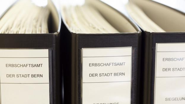 Drei Bundesordner zeigen ein Büro, worin Testamente abgelegt werden.