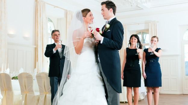 ein Festlicher Saal, darin im Vordergrund ein Brautpaar in Weiss und Frack, dahinter links ein Mann, rechts zwei Frauen - die Trauzeugen.