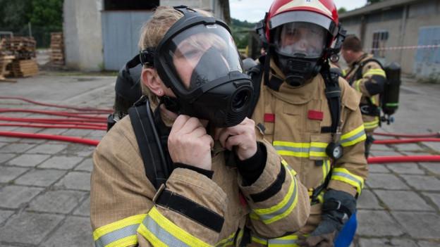 Zwei Feuerwehrleute in khaki-farbener Uniform mit Helmen und Atemschutzmaske an einer Rettungsübung in Chiasso