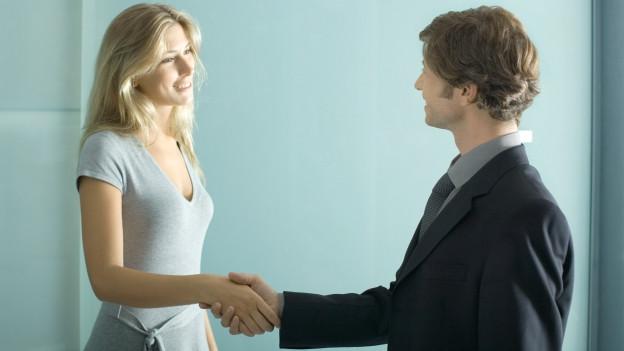 Frau und Mann geben sich die Hände.