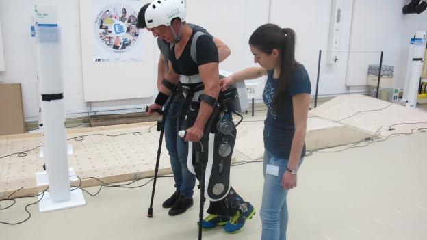 Philipp Wipfli, der sonst im Rollstuhl sitzt, trägt einen Roboteranzug, mit dem er aufrecht gehen kann.