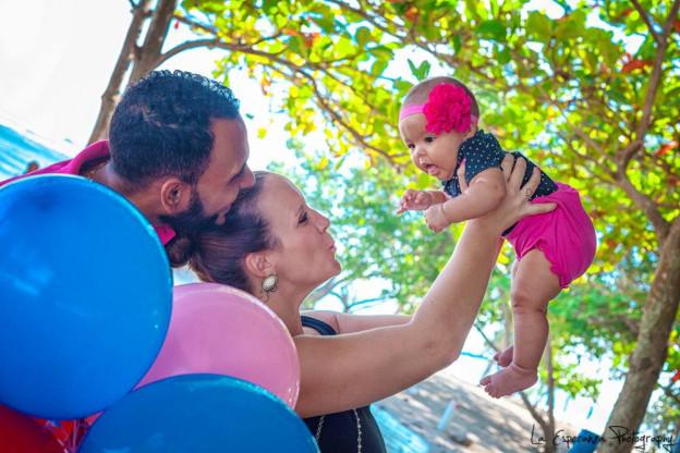 Anni Martinez zusammen mit ihrem Mann Carlos und Töchterchen Bayley. Das Mädchen trägt eine rote Schlaufe im Haar. Das Paar hält es hoch und ist sichtlich stolz.