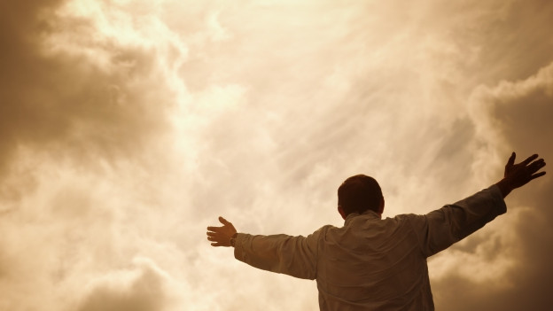 Mann streckt seine Arme gegen den Himmel.