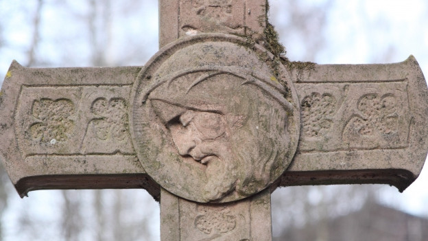 Jesusfigur auf Grabstein.