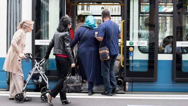 Frau mit Kopftuch steigt ins Tram.