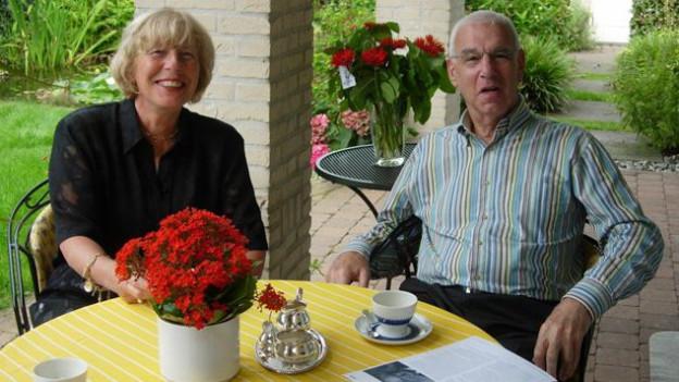 Susi De Groot und ihr Mann Philip sitzen an einem Tisch im Garten und trinken Tee.