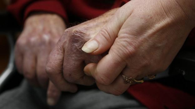 Eine jüngere Person hält einem ältern Mensch die Hand.
