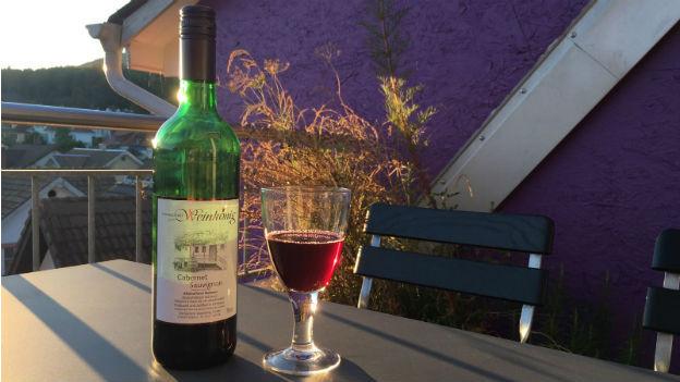 Eine Flasche alkoholfreier Rotwein mit Glas stehen auf einem Tisch im Abendlicht.
