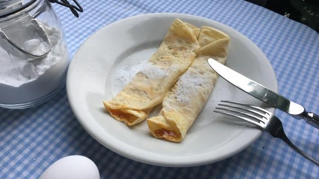 Zwei Palatschinken mit Aprikosenkonfitüre gefüllt auf einem Teller.