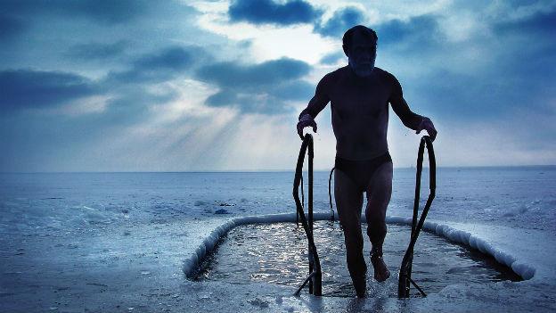 Ein Mann in Badehose steigt im Winter aus dem kalten Wasser.