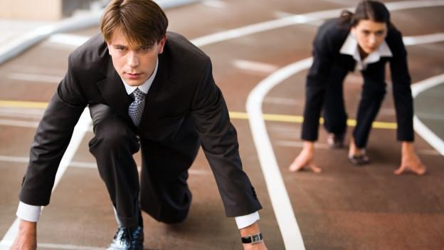 Eine Tartan-Rennbahn, darauf rennen eine Frau und ein Mann im Business-Anzug.