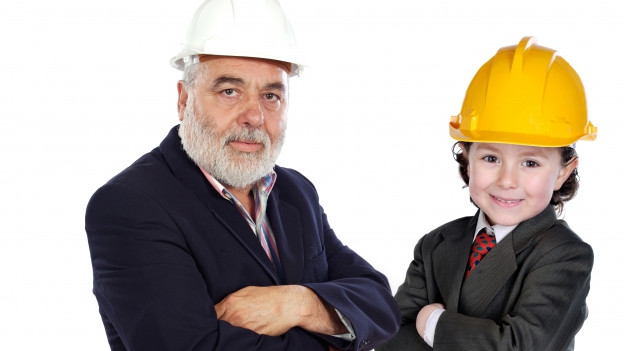 Ein Grossvater und sein Enkel stehen, gut gekleidet, aber mit Bauhelm auf den Köpfen
